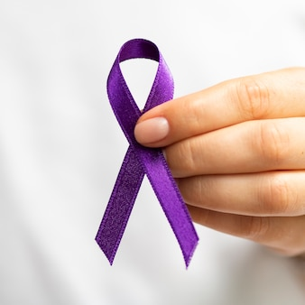 Close-up woman holding up purple ribbon