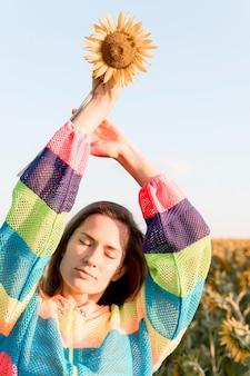 Крупным планом женщина держит подсолнух
