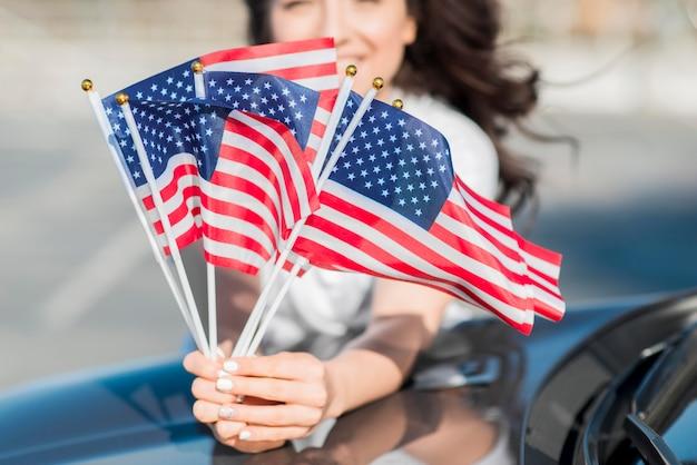 Женщина конца-вверх держа флаги сша на автомобиле