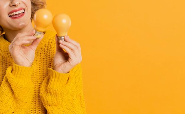 Close-up woman holding yellow bulbs