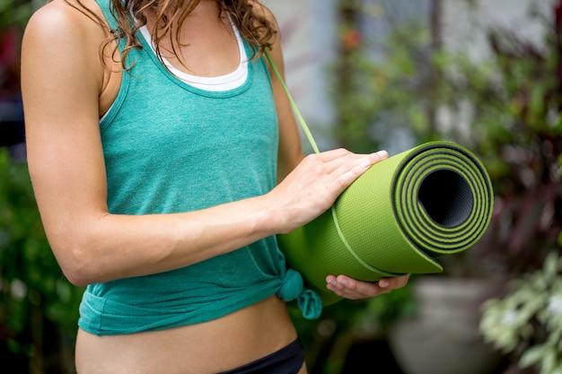 Close-up of woman holding yoga mat outdoors