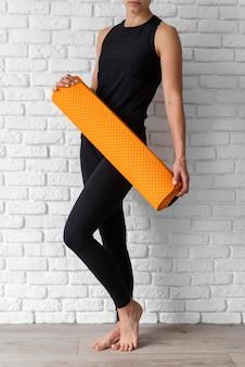Крупным планом женщина, держащая коврик для йоги