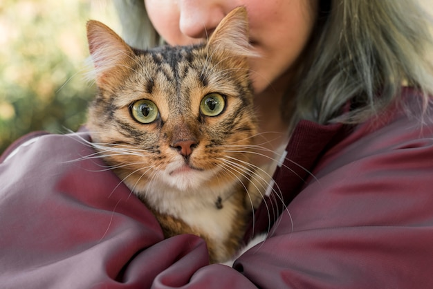 Close-up of a woman hugging her tabby cat