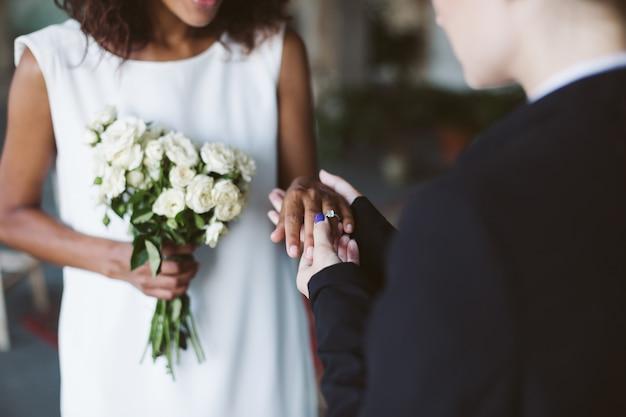結婚式で白いドレスを着た美しいアフリカ系アメリカ人の女性に結婚指輪を置く黒いスーツの女性をクローズアップ