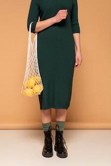 Крупным планом женщина в повседневной одежде, несущая многоразовую сумку с черепахой