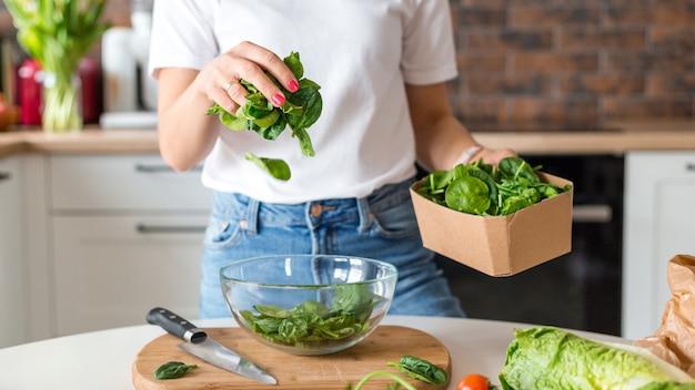 집 부엌에서 동작 효과가 있는 흰색 티셔츠 요리 샐러드를 입은 여성을 클로즈업하세요. 건강 식품, 야채 샐러드 개념을 요리하는 과정. 메뉴, 레시피 북 배너