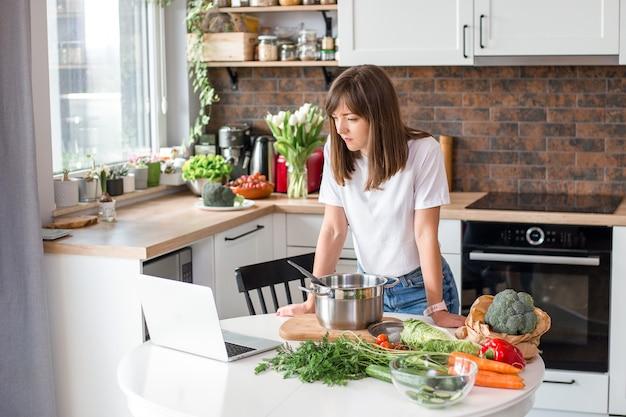 집에서 신선한 야채와 함께 수프를 요리 하는 흰색 티셔츠에 여자를 닫습니다. 메뉴, 조리법 책 배너입니다. 소녀는 노트북에서 조리법을 읽습니다. 로프트 아파트에서 인터넷을 사용하는 백인 모델입니다.