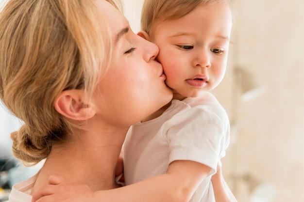 Крупным планом женщина целует ребенка