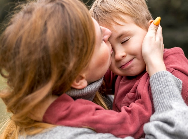 Close-up woman kissing son
