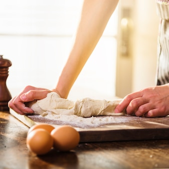 Close-up of woman kneading the dough on chopping wooden board