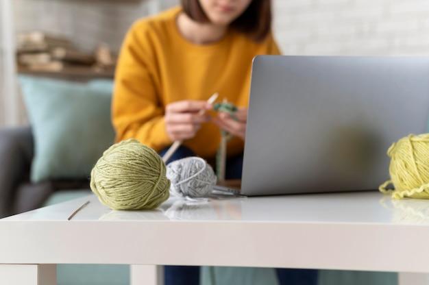 집에서 뜨개질하는 여자를 닫습니다