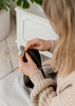 Donna del primo piano che lavora a maglia con gli aghi metallici