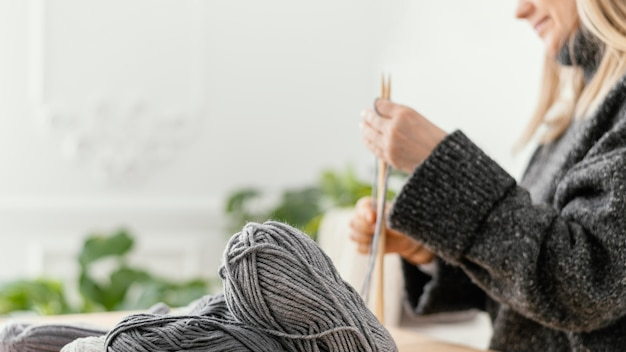 Close-up woman knitting with needles