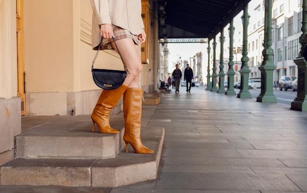 Закройте ноги женщины в красных сапогах на высоком каблуке и на улице города лестницы. модный наряд