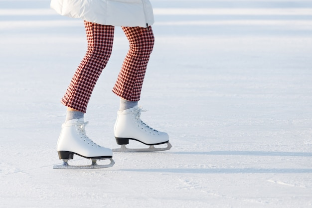 Close up of woman legs in red checked trousers on skates on an open skating rink, copy space. sunny day.