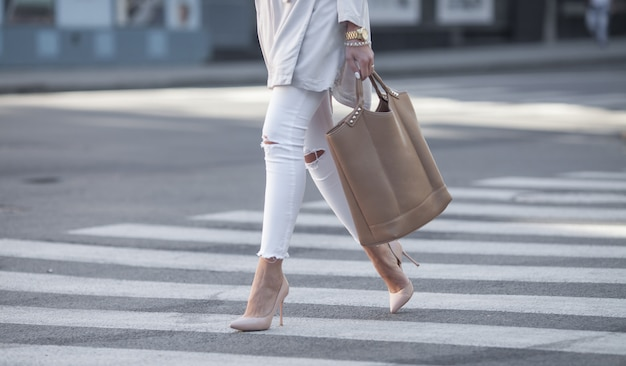 Close up of woman legs walking on crosswalk. the woman is wearing shoes on high heels.