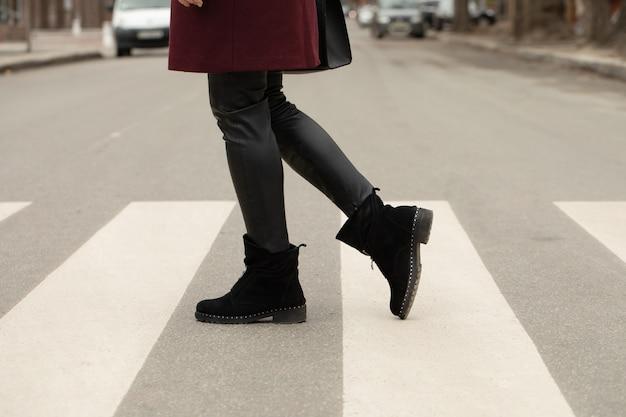 Close up of woman legs walking on crosswalk.