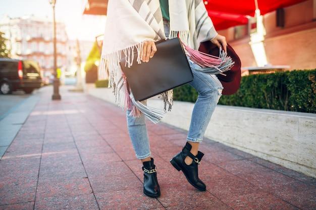 Primo piano di gambe di donna che indossa stivali di pelle nera, jeans, tendenze primaverili di calzature, borsa della holding