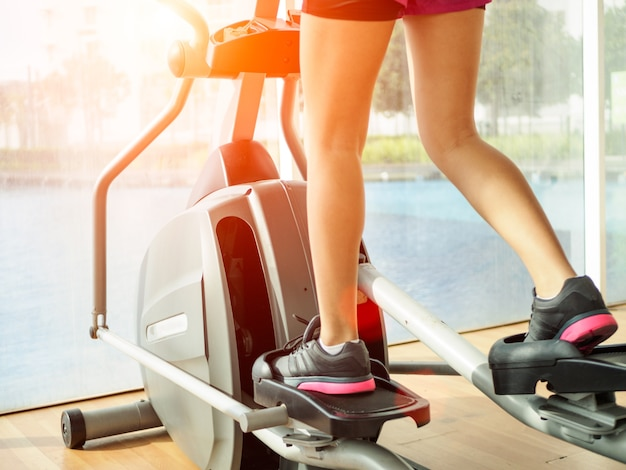 Close up woman legs working out on the exercise bike in fitness gym.