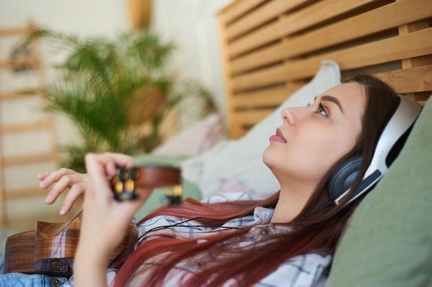 クローズアップの女性は、ヘッドフォンで音楽を聴き、ウクレレを演奏し、ベッドに横になります。