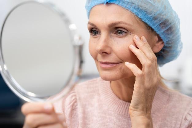 Крупным планом женщина смотрит в зеркало
