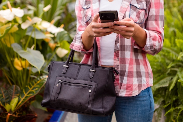 Close-up woman looking at phone in greenhouse