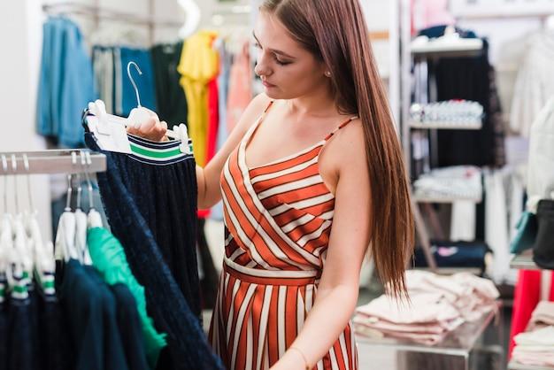 Close-up woman looking at a skirt