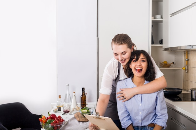 Close-up of a woman loving his friend looking at recipe on clipboard in the kitchen