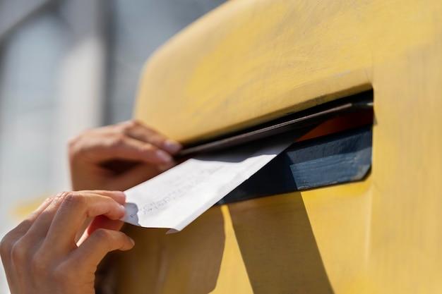 Chiuda sulla donna alla cassetta postale con la busta