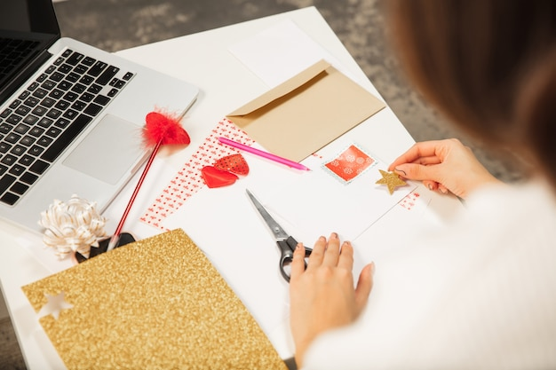 친구 또는 가족, 스크랩 예약, diy를 위해 새해 및 크리스마스 2021 인사말 카드를 만드는 여자를 닫습니다. 최고의 소원을 담은 편지를 쓰고 수제 카드를 디자인하십시오. 휴일, 축하.