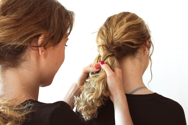 Close-up of woman making her sister's braid against white background