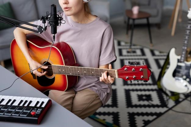 Donna ravvicinata che fa musica a casa