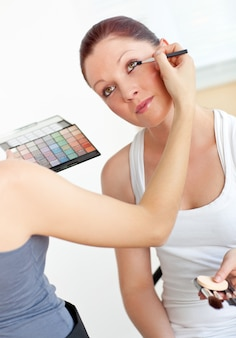 Close-up of a woman making-up her female friend at home