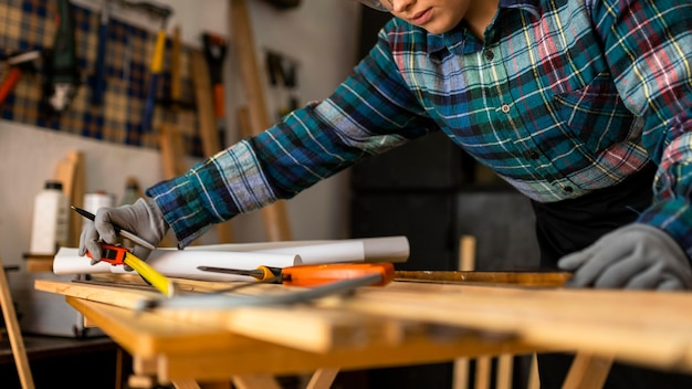 Close up woman measuring wood plank