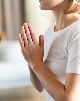 Крупным планом женщина медитирует в помещении