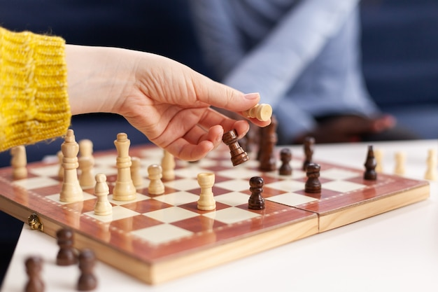 Close up of woman moving chess pieces on board during global pandemic with coronavirus. group of friends having fun in home living room. conceptual image. board games, competing, tactics, asctivity.