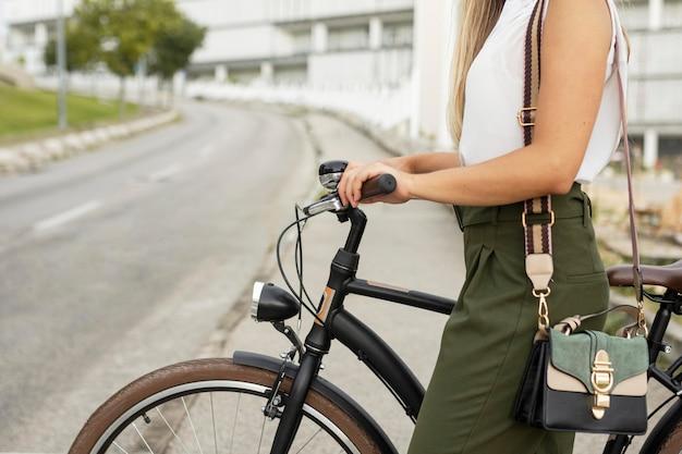 Женщина крупным планом рядом со своим велосипедом