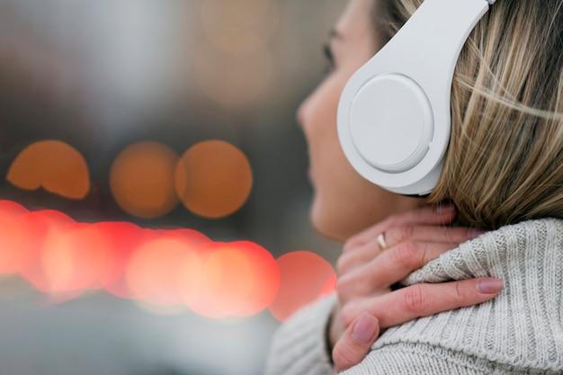 Женщина конца-вверх на крыше держа heaphones на головной форме позади