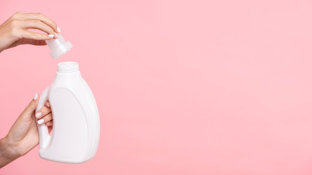 Close-up woman opening detergent bottle