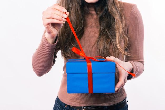 흰색 배경 위에 선물 상자를 여는 여자를 닫습니다