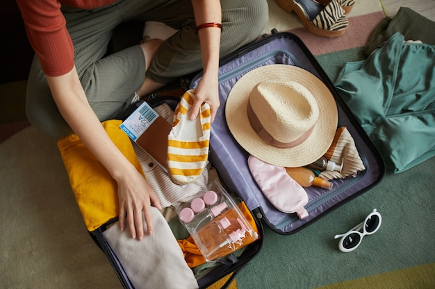 Close-up of woman packing her clothes in suitcase she is going in summer vacation