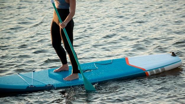 Close upwoman paddleboarding