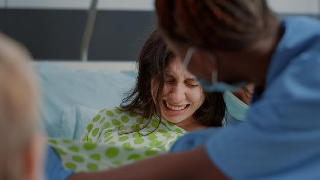 Primo piano di una donna in travaglio doloroso che dà alla luce un bambino