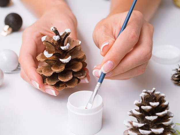 Close-up of woman painting pine cone