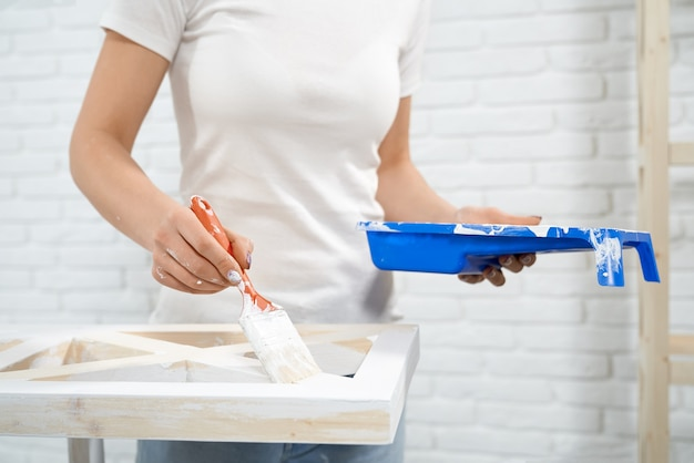 Close up of woman painting wooden storage stand