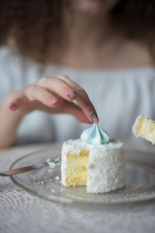 Close-up of woman picking up the merengue over the cake on plate