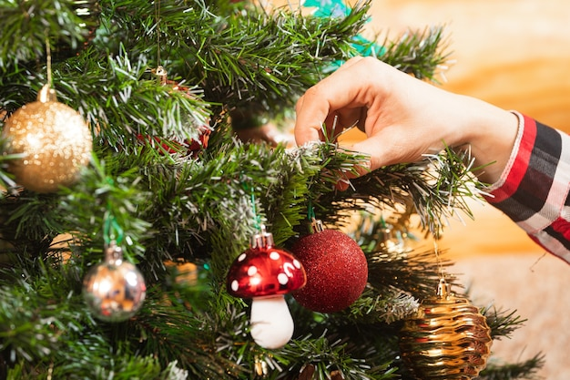 Close-up of a woman in a plaid shirt hangs a beautiful shiny red ball on a christmas tree