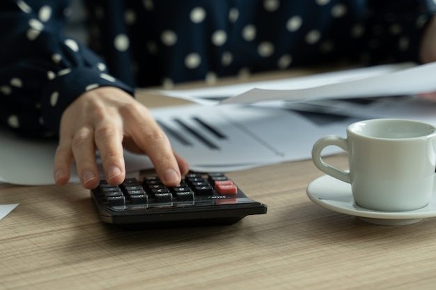 Крупным планом женщина, планирующая бюджет, используя калькулятор и ноутбук, читая документы, сидя за столом
