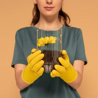플라스틱 병에 여자 심은 꽃을 닫습니다