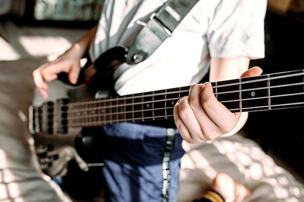 Крупным планом женщина играет на бас-гитаре
